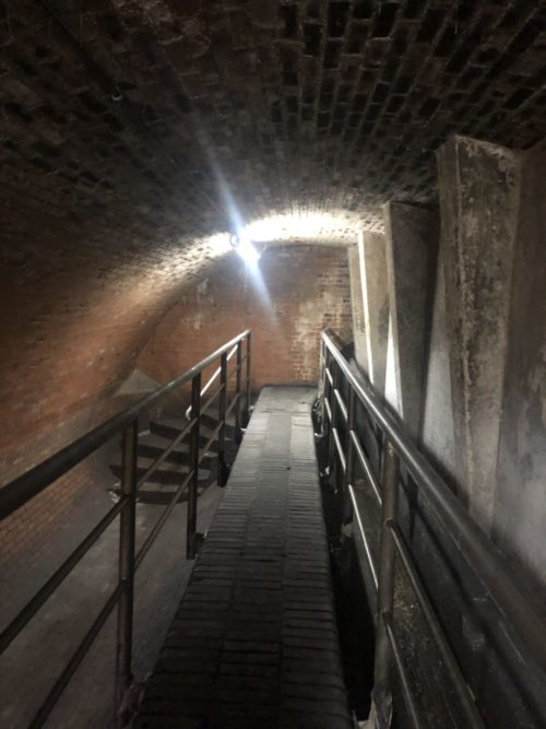 Dunkles Kellergewölbe mit langer Holzbrücke