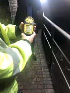 Gasmessgerät in der Hand einer Person in einer neonfarbenen Jacke