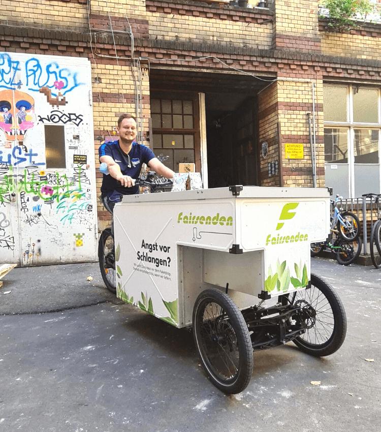 Fairsenden Fahrradkurier mit Lastenrad im Hinterhof