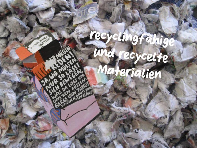 """Bild eines Altpapierhaufens mit der einhorn Tampon Verpackung und der aufschrift """"recyclingfähige und recycelte Materialien"""""""