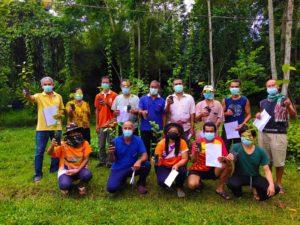 Eine Gruppe von Kautschuk-Kleinbauern und -Kleinbäuerinnen in Thailand mit Baumsetzlingen in den Händen